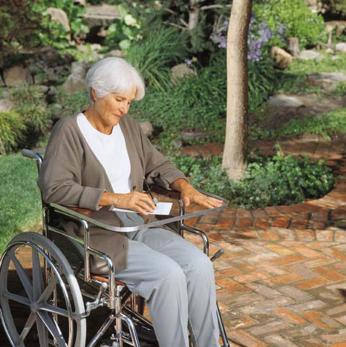 mujer mayor con una mesita en la silla de ruedas