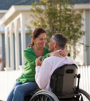 pareja feliz abrazandose, hombre en silla de ruedas manual