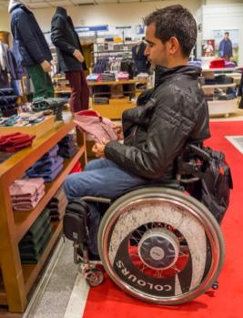 hombre joven comprando una camisa, va en silla de ruedas con accesorios
