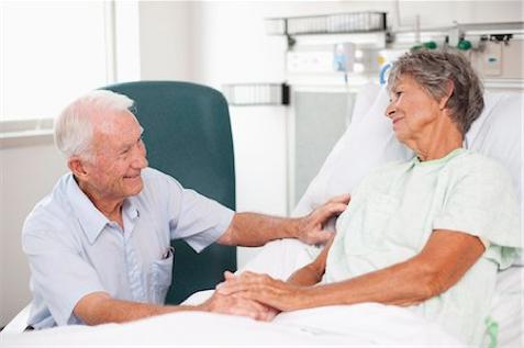 dos personas mayores, la mujer en una cama ortopedica