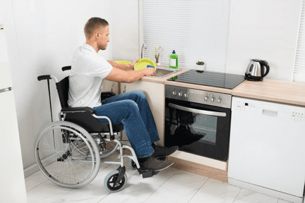 hombre en silla de ruedas lavando platos