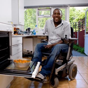 persona en silla de ruedas poniendo el horno