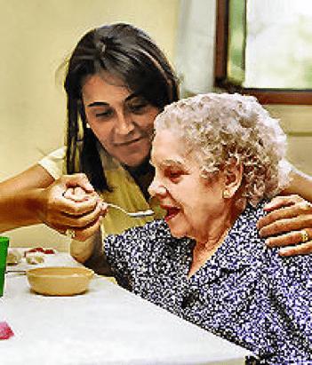 una asistente da a una anciana la comida