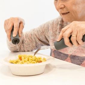 una mujer come pasta con cubiertos adaptados