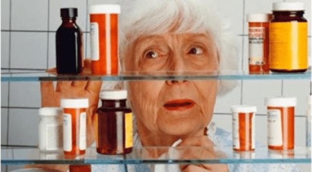 se ve a una mujer asustada al abrir el armario y ver muchos botes de pastillas