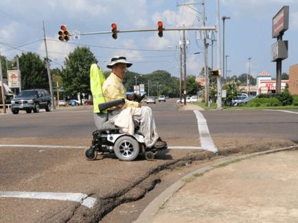 usuario en silla de ruedas electrica con aceras sin rebajar