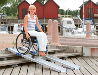 usuario ensilla de ruedas bajando escaleras mediante rampas telescopicas