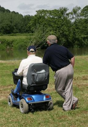 dos amigos, uno caminando con una scooter