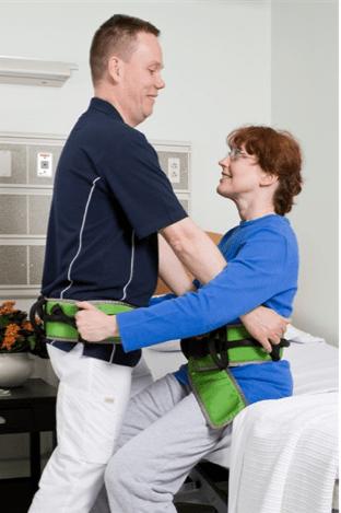se ve a una asistente transfiriendo a una persona con discapacidad