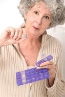 mujer recogiendo una pastilla medica del pastillero