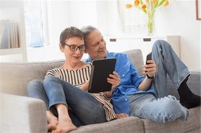 imagen de dos personas mayores viendo su tablet en el sofa